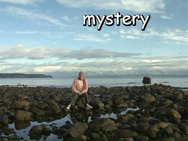 "the word ""mystery"" with Marie sitting among the beach rocks"
